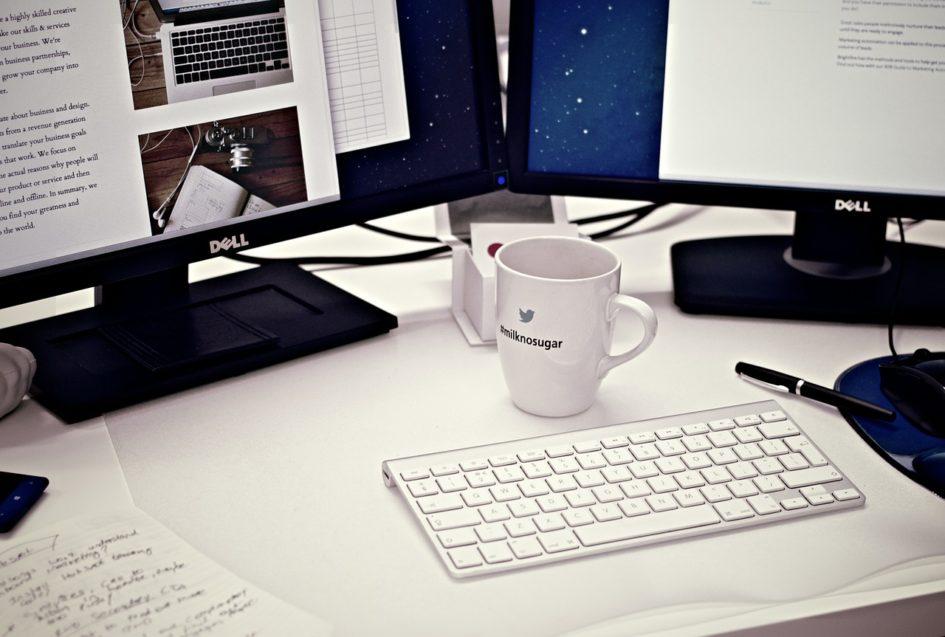 Computador e xícara de café na mesa