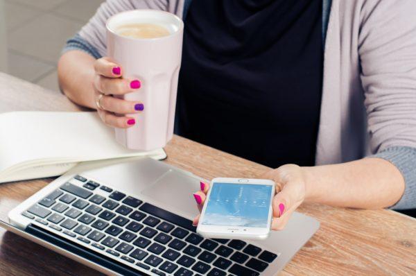 Tomando café e usando o smartphone e macbook